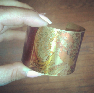 A Printed Brass cuff from Odd Bird. Featuring this classic image layered sheerly over a lightweight brass cuff. Fully adjustable!